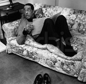 The American jazz pianist and composer Duke Ellington (1899-1974) relaxes at home as he examines some sheet music. 1963
